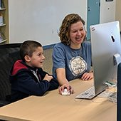 librarian and kid working at a computer