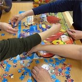 people completing a puzzle