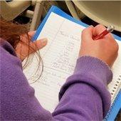 kid writing in notebook