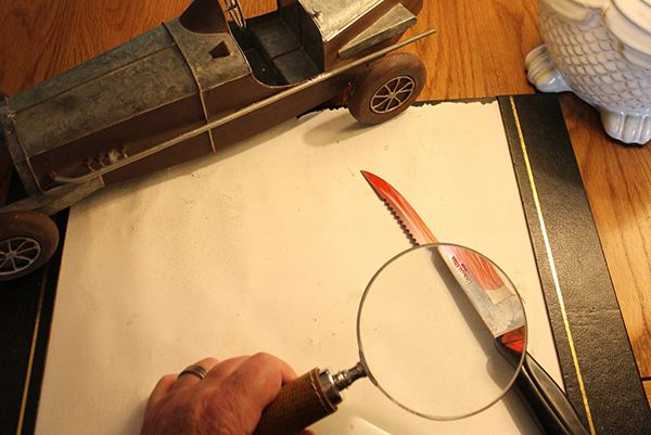 desk with bloody knife and magnifying glass