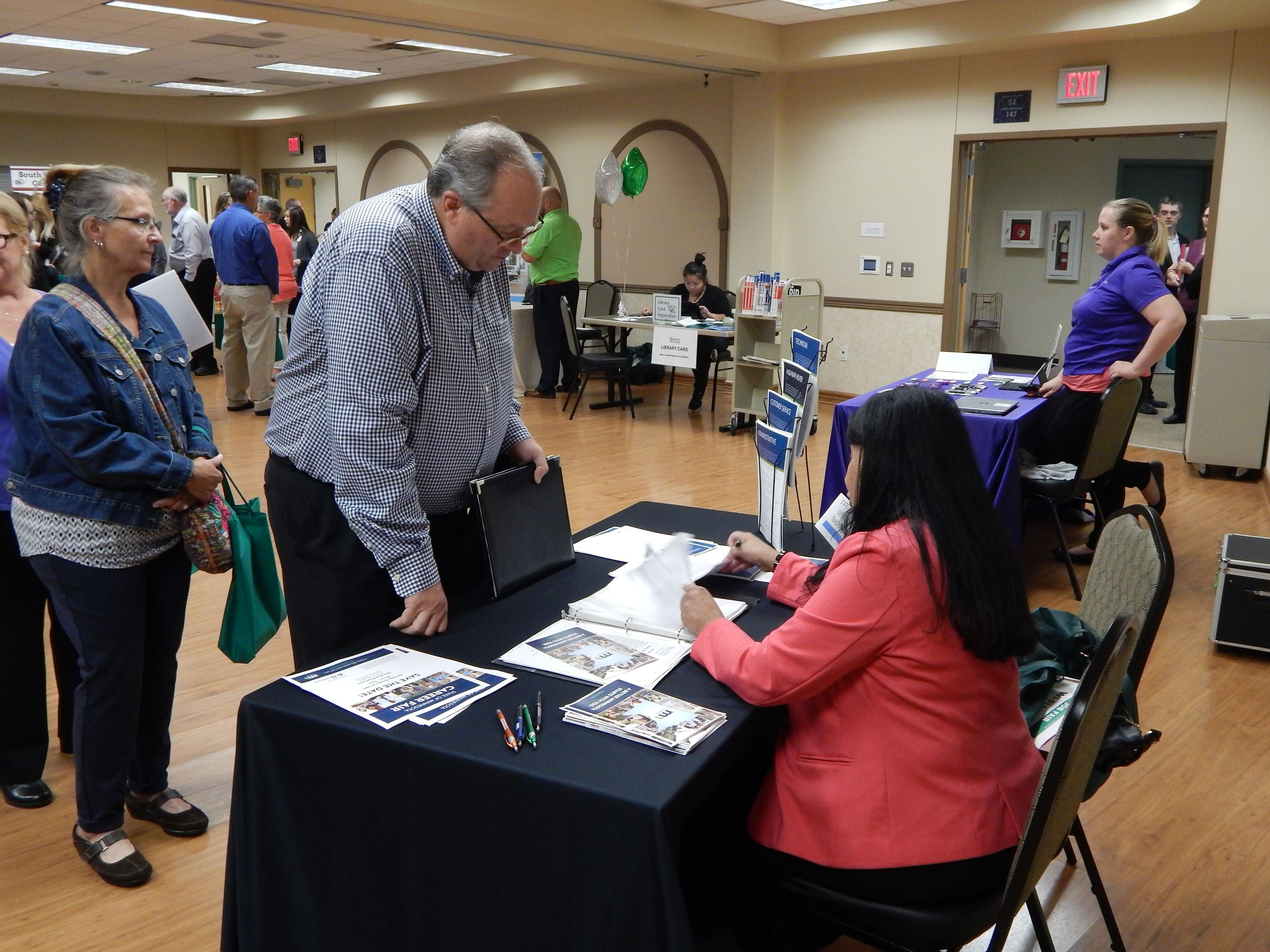 Photo of people tabling at a job fair.