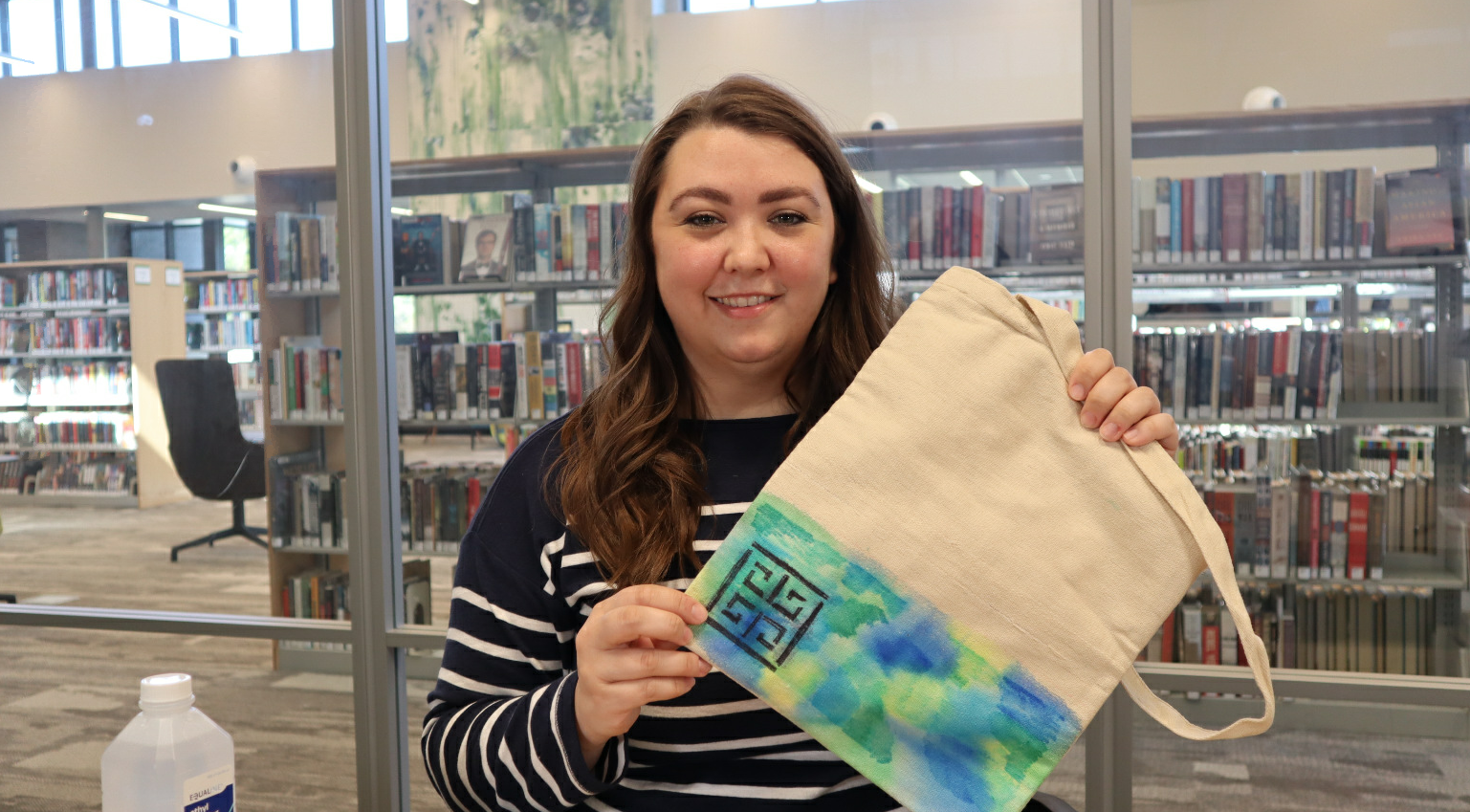 Woman holding a tie-dyed bag.